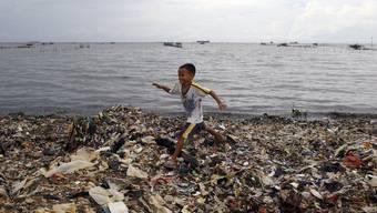 Ein indonesischer Junge läuft am Strand von Jakarta über einen Teppich von Abfall (Archiv)