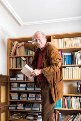 «I holes schnäll abe»: Franz Hohler mit dem «Abrogans»-Faksimile vor seinem Bücherregal in Oerlikon.severin bigler