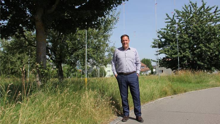 Martin Meyer steht in Lupfig vor der mit Bauprofilen versehenen Parzelle der Wohnbaugenossenschaft Lägern.