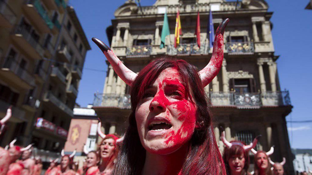 Gehörnte und rot bemalte Frauen protestieren in Pamplona gegen die Stierhatz