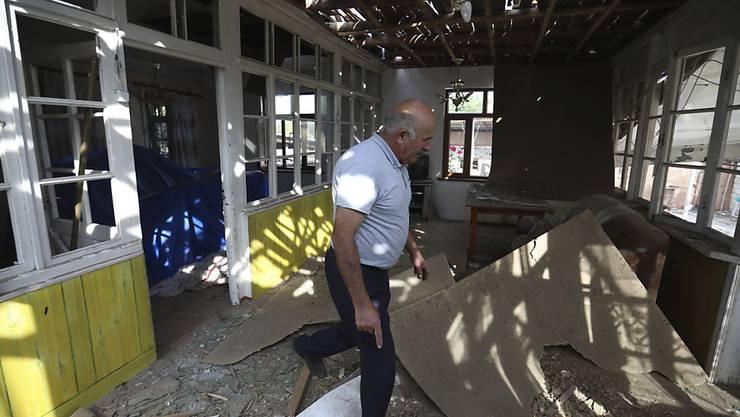 Nach Angriffen armenischer Truppen inspiziert ein Mann sein beschädigtes Haus im aserbaidschanischen Tartar. Foto: Aziz Karimov/AP/dpa