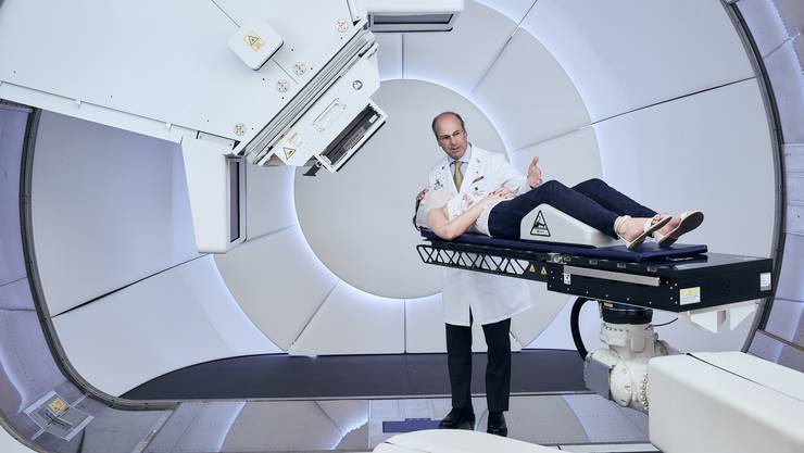Prof. Damien Weber, Leiter des Zentrums für Protonentherapie am Paul Scherrer Institut, bereitet eine Patientin für die Behandlung an der Gantry 3 vor. (Foto: Scanderbeg Sauer Photography)