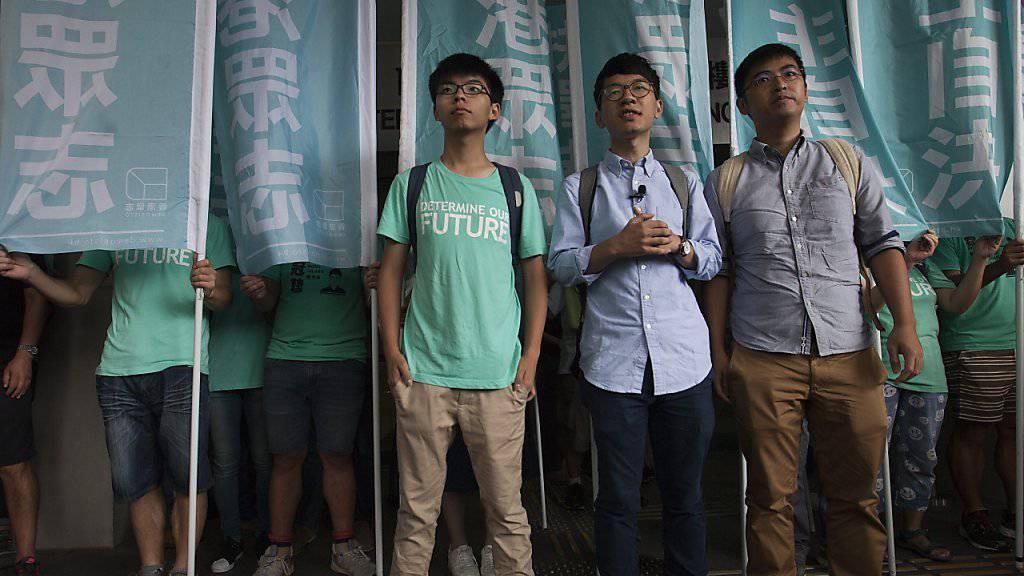 """Die Studenten Joshua Wong (links), Nathan Law (Mitte) und Alex Chow (rechts) vor dem Gericht in Hongkong, das sie wegen ihrer Rolle bei der """"Regenschirm-Revolution"""" zu Sozialdienst und einer Bewährungsstrafe verurteilte."""