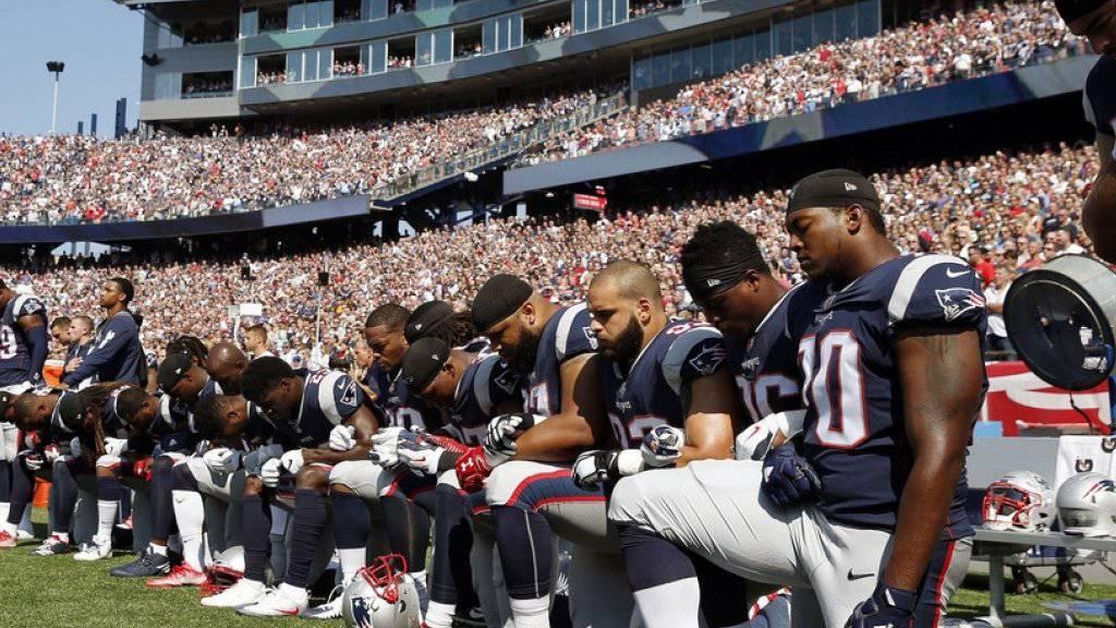 Aus Protest gegen Rassismus und die verbalen Attacken von US-Präsident Donald Trump knieten 15 Football-Spieler der New England Patriots während der Nationalhymne am Boden.
