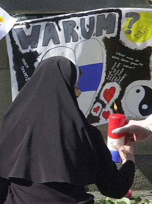Eine Nonne zündet am Tag nach dem Attentat eine Kerze vor dem Parlamentsgebäude im Gedenken an die Opfer an