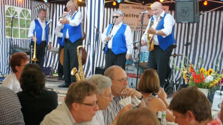 Während sich die Zuschauer auf dem Dorfplatz verpflegen, geben die Piccadilly Six auf der Bühne ihr Bestes. Foto: Mmo