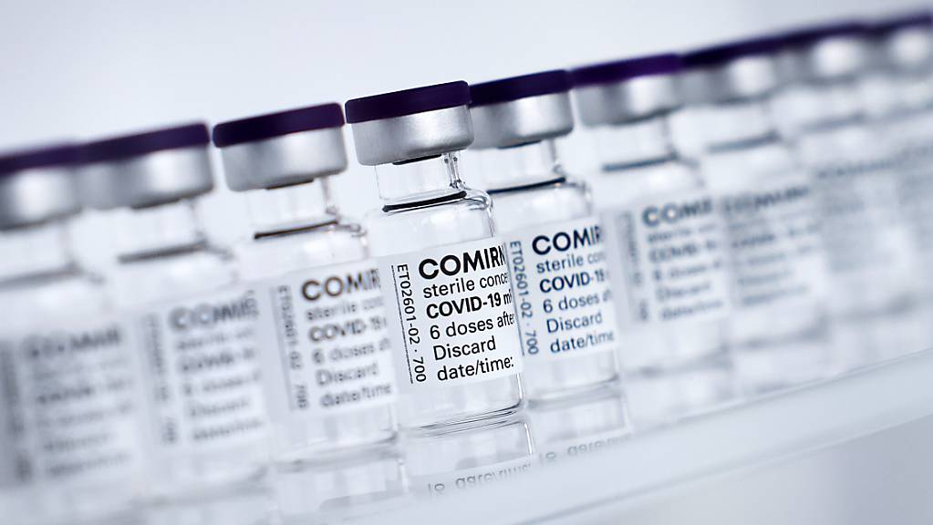Fläschchen mit dem Impfstoff Comirnaty von Biontech/Pfizer stehen auf einem Tisch.