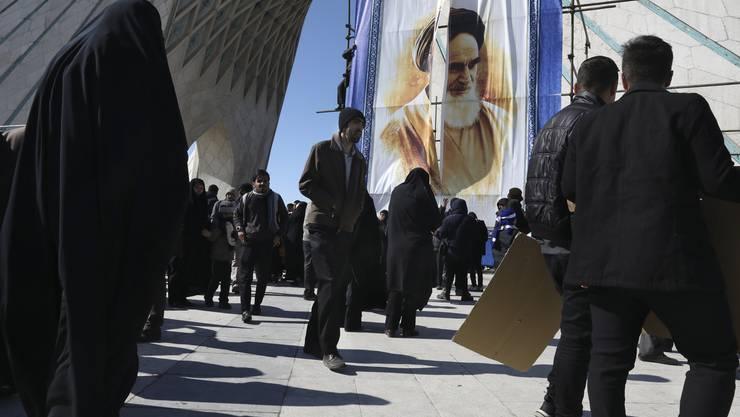 Iraner feiern in Teheren den 41. Jahrestag der Isalmischen Revolution. Im Hintergrund prangt das Porträt von Revolutionsführer Ajatollah Chomeini.