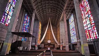 Blick durch das farbig erleuchtete Schiff der Antoniuskirche mit den modern anmutenden Fenstern.
