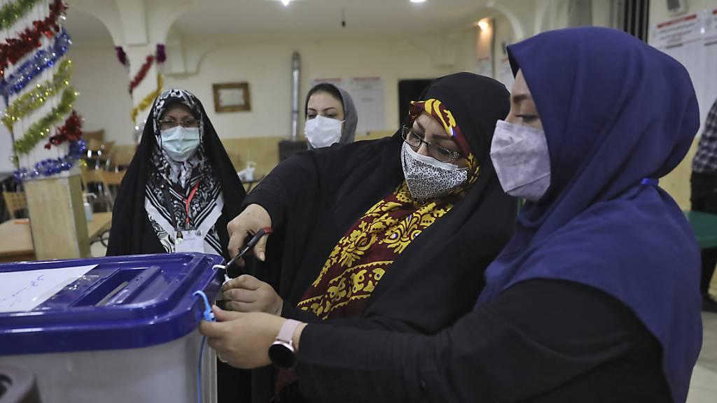 Wahlhelferinnen öffnen eine Wahlurne in einem Wahllokal. Foto: Vahid Salemi/AP/dpa