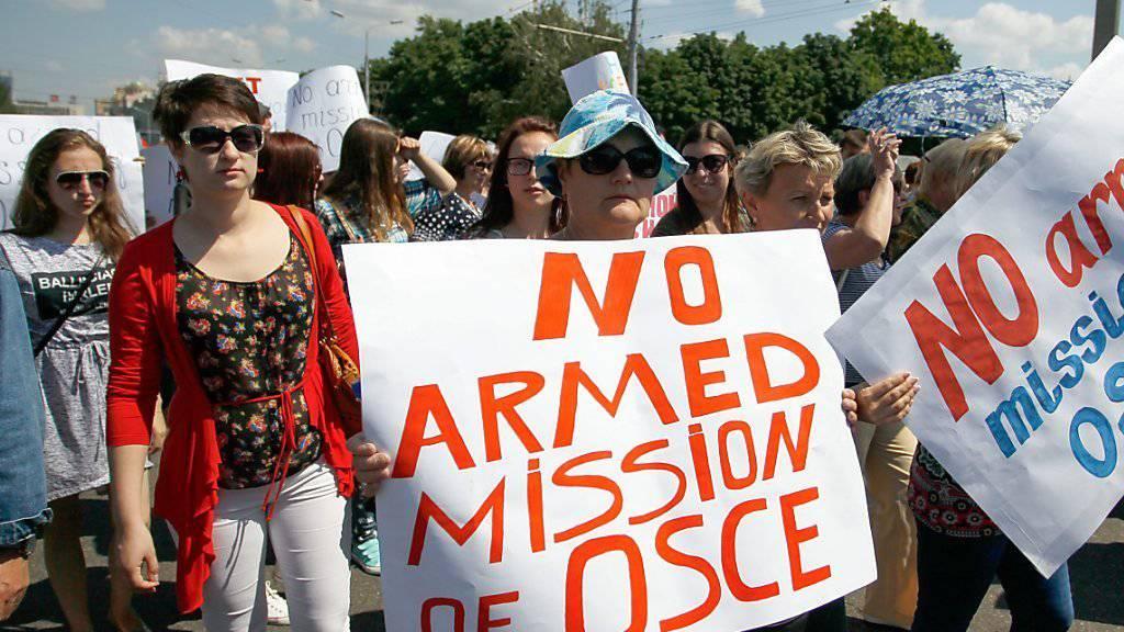 Die Demonstrierenden in Donezk sind nicht damit einverstanden, dass die OSZE-Beobachter in der Ostukraine bewaffnet werden sollen.