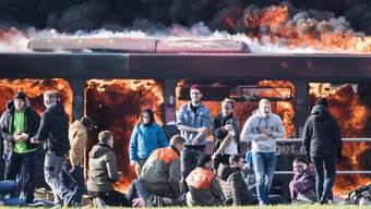 Figuranten warten vor einem simuliert gesprengten Personenbus auf die Rettungskraefte, waehrend der Flughafenuebung 'Speed17'.