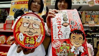 Zwei Maids präsentieren Snacks mit dem Abbild des Premierministers.