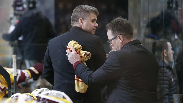 Genfs Trainer Chris Mcsorley reinigt die Jacke seines Assistenztrainers Louis Matte nach einer Bierdusche aus dem Publikum.