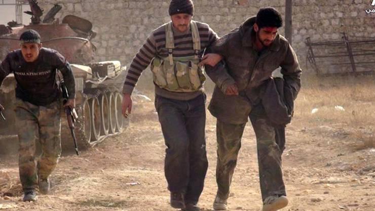 Kämpfer bei Aleppo helfen einem verwundeten Kameraden: Die USA bilden Rebellen in Syrien aus und wollen weitere Spezialeinheiten ins Kriegsgebiet schicken. (Symbolbild)