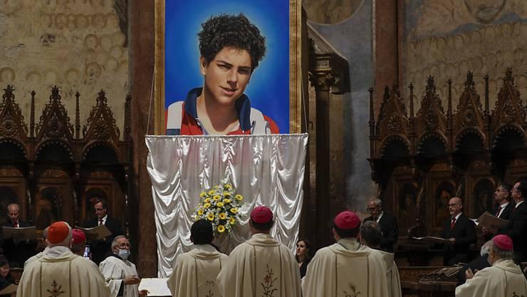 Ein Foto des 15-jährigen Carlo Acutis, der 2006 an Leukämie verstorben ist, wird bei seiner Seligsprechung in der Basilika San Francesco enthüllt. Foto: Gregorio Borgia/AP/dpa