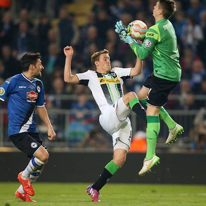 Gladbachs Max Kruse (m.) von Bielefeld-Goalie Schwolow gestoppt