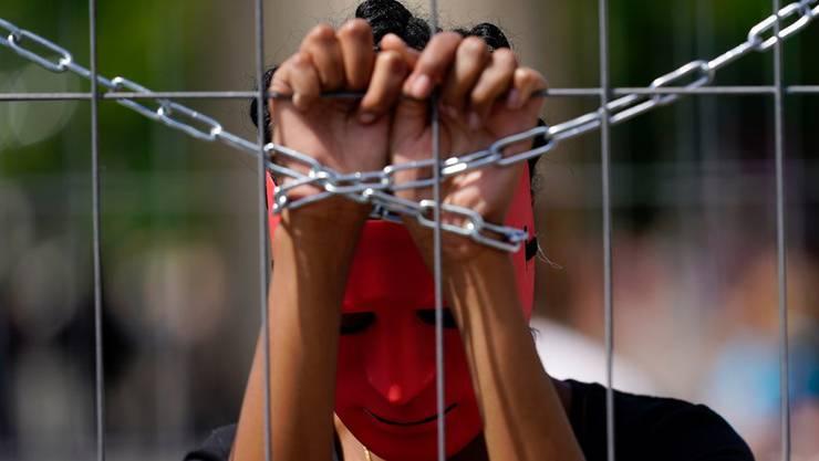 Ein Aktivist demonstriert in Brandenburg gegen Zwangsarbeit und Zwangsprostitution.