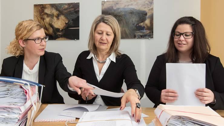 Die Anklägerinnen Tanja Fuchs, Susanne Steinhauser und Sabine Schwarzwälder zwischen Akten und Raubtier-Bildern.