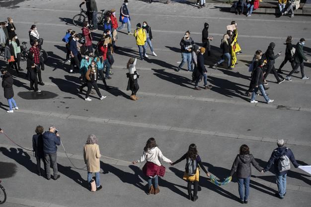 «Querdenker» bilden eine Menschenkette, eine Gegendemo zieht vorüber.