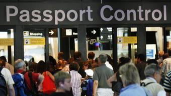 Reisende stehen bei der Passkontrolle in der Schlange (Symbolbild)