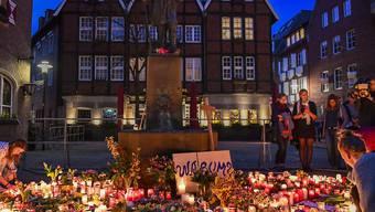 Menschen gedenken mit Kerzen der Opfer in Münster.