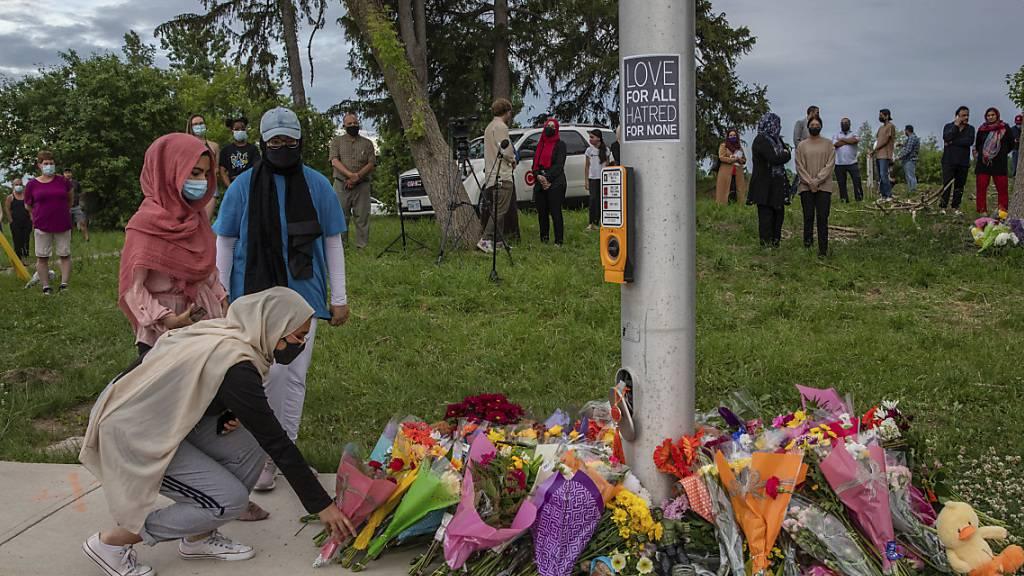 Trauernde legen Blumen an der Stelle ab, wo eine fünfköpfige Familie von einem Autofahrer angefahren wurde, in London, Ontario. Foto: Brett Gundlock/The Canadian Press via AP/dpa - ACHTUNG: Nur zur redaktionellen Verwendung und nur mit vollständiger Nennung des vorstehenden Credits