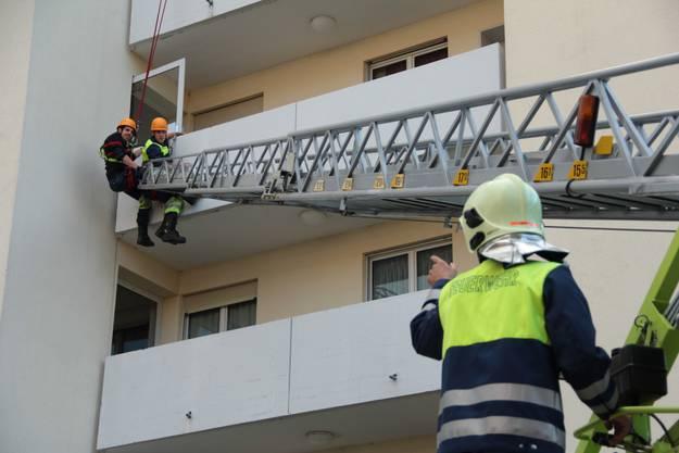 Schwindelnde Höhen Vom Dach klettert ein Feuerwehrmann auf den dritten Stock hinunter um einen Verunfallten zu bergen