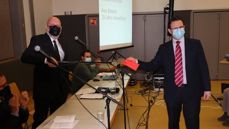 Geschenkübergabe aus Distanz: Gemeindeammann Erich Hunziker (l.) übergibt mit der Abfallzange ein Couvert an Alex Bissola.
