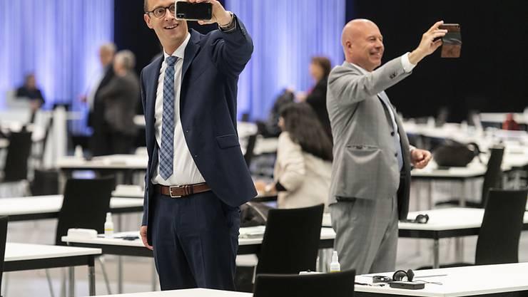 Martin Candinas (CVP/GR), links, und Fabio Regazzi CVP/TI, machen Selfies am ersten Tag der ausserordentlichen Session der Eidgenössischen Räte zur Corona-Krise im Nationalrat in einer Ausstellungshalle der Bernexpo in Bern.