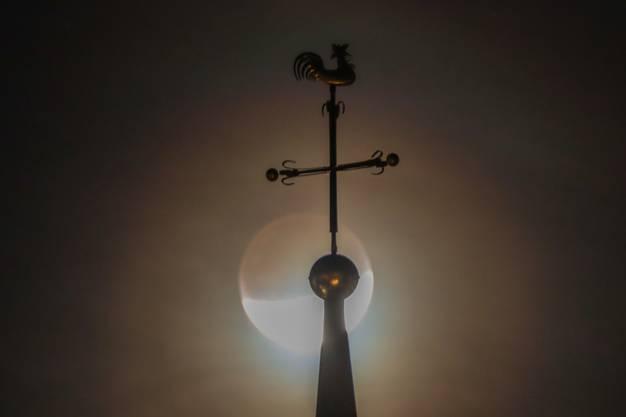 Der Mond zieht seine Bahn hinter der Kirchturmspitze von Muttenz.