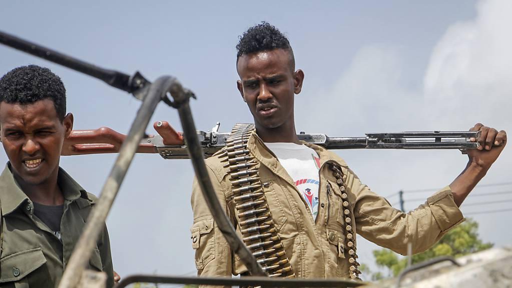 Sicherheitskräfte betrachten die Trümmer nach einem Anschlag auf den Polizeichef von Mogadischu. Foto: Farah Abdi Warsameh/AP/dpa