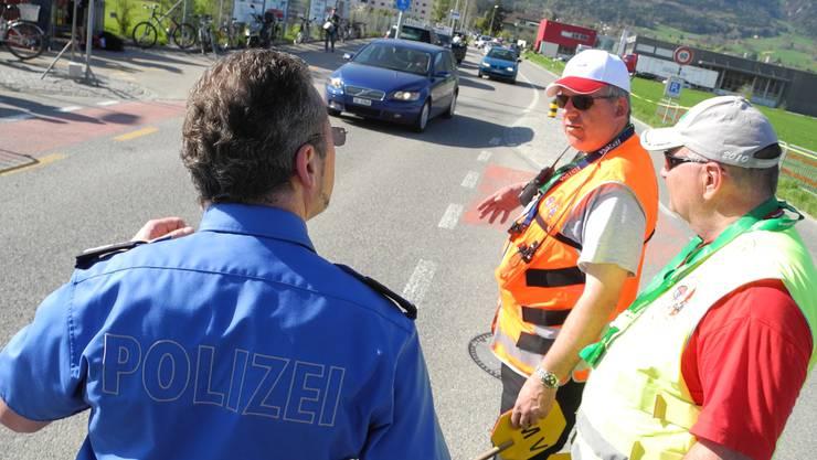 Einsatzleiter Michael Herzog (l.) diskutiert mit Tour-Sicherheitsleuten, kurz vor dem grossen Verkehrs-Rückstau wegen der Zieleinfahrt.