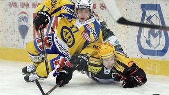 Martin Plüss (unten) und der Davoser Perttu Lindgren kämpfen um die Scheibe.