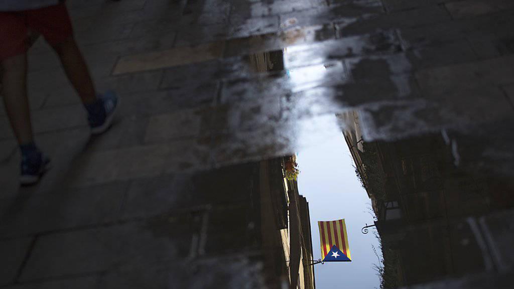Eine katalanische Flagge spiegelt sich in einer Pfütze in Barcelona. Die Rhetorik im Konflikt um die spanische Region Katalonien verschärft sich.