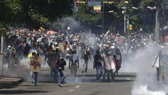 Demonstranten in Caracas werden von Polizisten mit Tränengas zurückgetrieben.
