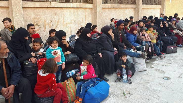 Zivilisten warten am Dienstag an einem Armeekontrollpunkt in Ost-Ghuta auf ihre Ausreise aus der belagerten Stadt.