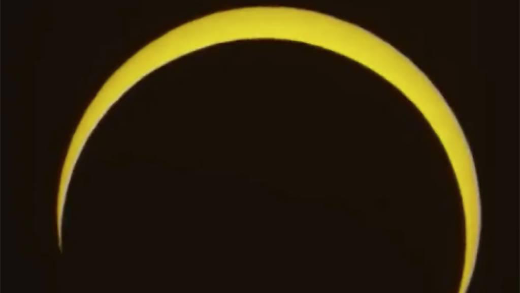 Menschen in Asien bestaunen ringförmige Sonnenfinsternis