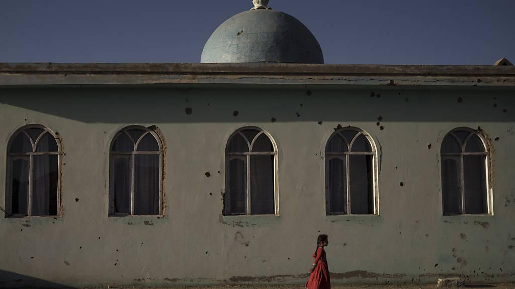 Ein Mädchen geht vor einer Moschee mit Einschusslöchern in einem Dorf in der afghanischen Provinz Wardak. Foto: Felipe Dana/AP/dpa
