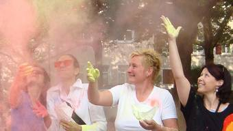 Die Organisatorinnen der Jugendfestkommission werfen Farbe in die Luft. zvg