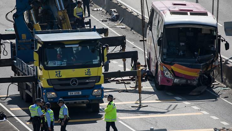 Nach der tödlichen Kollision zwischen einem Bus und einem Taxi in Hongkong räumen Arbeiter das Buswrack von der Autobahn.