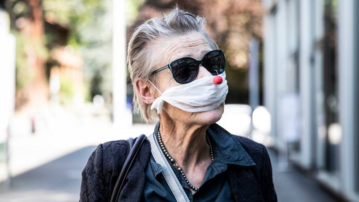 Eine pragmatische Fatalistin? Eine Frau mit einer selbstgemachten Maske und roter Clownnas, Ende April in Kriens.