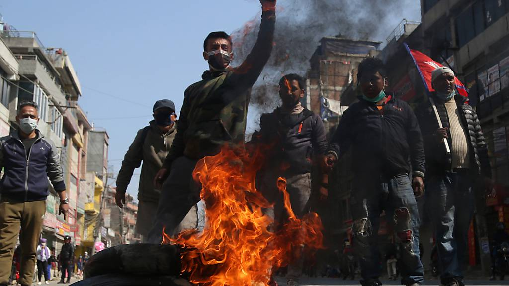 Demonstranten blockieren mit brennenden Reifen eine Straße während eines Generalstreiks. Ein Generalstreik, der von einer Splittergruppe der regierenden kommunistischen Partei ausgerufen wurde, hat das Leben weitestgehend beeinträchtigt. Schulen, Transportmittel, Märkte wurden bestreikt. Foto: Dipen Shrestha/ZUMA Wire/dpa