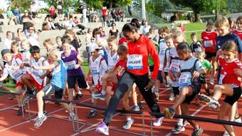 Olympiasiegerin Melaine Walker übt mit den Kindern die richtige Hürdentechnik.