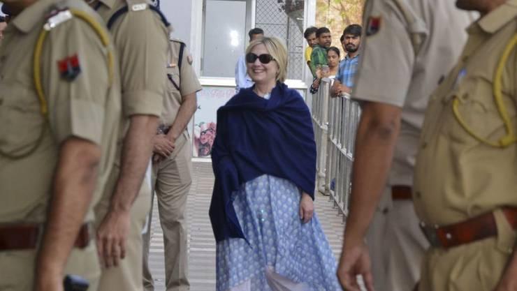 Hillary Clinton am Donnerstag auf dem Flughafen Jodhpur. Die bandagierte Hand verbirgt sie diskret unter dem Cape. Sie hatte sich einen Haarriss zugezogen, als sie in der Hotel-Badewanne ausrutschte.