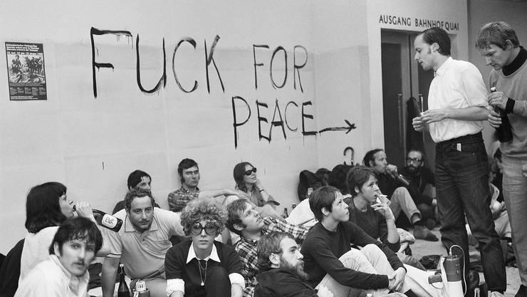 Junge Leute sitzen im besetzten Globus-Provisorium in Zuerich, Schweiz, am Boden, aufgenommen 16. Juni 1968, in der Mitte mit Brille die Aktivisitin Andrée Valentin.