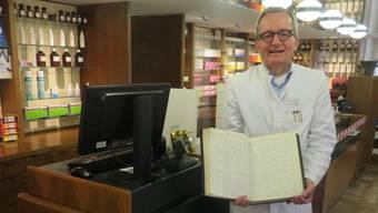 Apotheker Andreas Külling mit einem Buch, in dem alle bezogenen Rezepte vom Oktober 1963 handschriftlich festgehalten.
