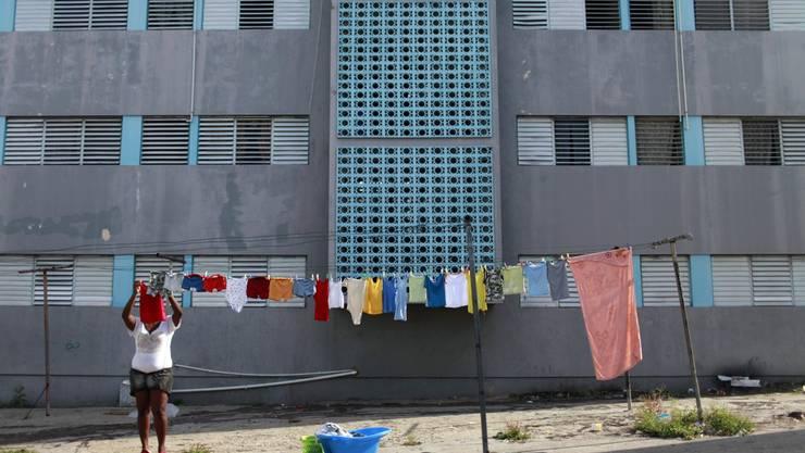Alltag in Jamaika: Eine Frau hängt Wäsche auf in einem Quartier in Kingston