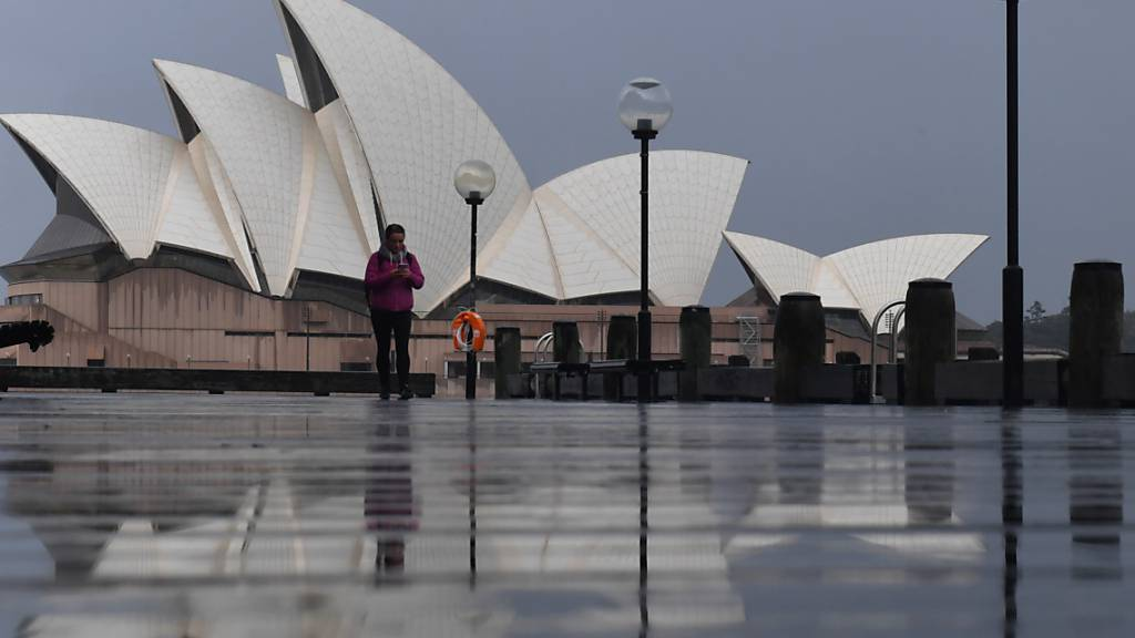 A pedestrian walks past the Sydney Opera House in Sydney, Saturday, July 10, 2021. Tough new restrictions are now in place for Greater Sydney after another spike in COVID-19 cases. (AAP Image/Mick Tsikas) NO ARCHIVING