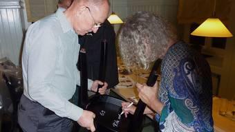 Der erste Genossenschafts-Präsident, Jörg Stolz und seine Ehefrau Rita, signieren «ihren» «Bären»-Stuhl. – Foto: ghi